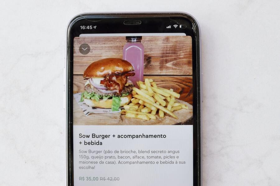 Tela de celular com um cardápio online exibindo um promoção de combo com hambúrguer com suco e batatas fritas.