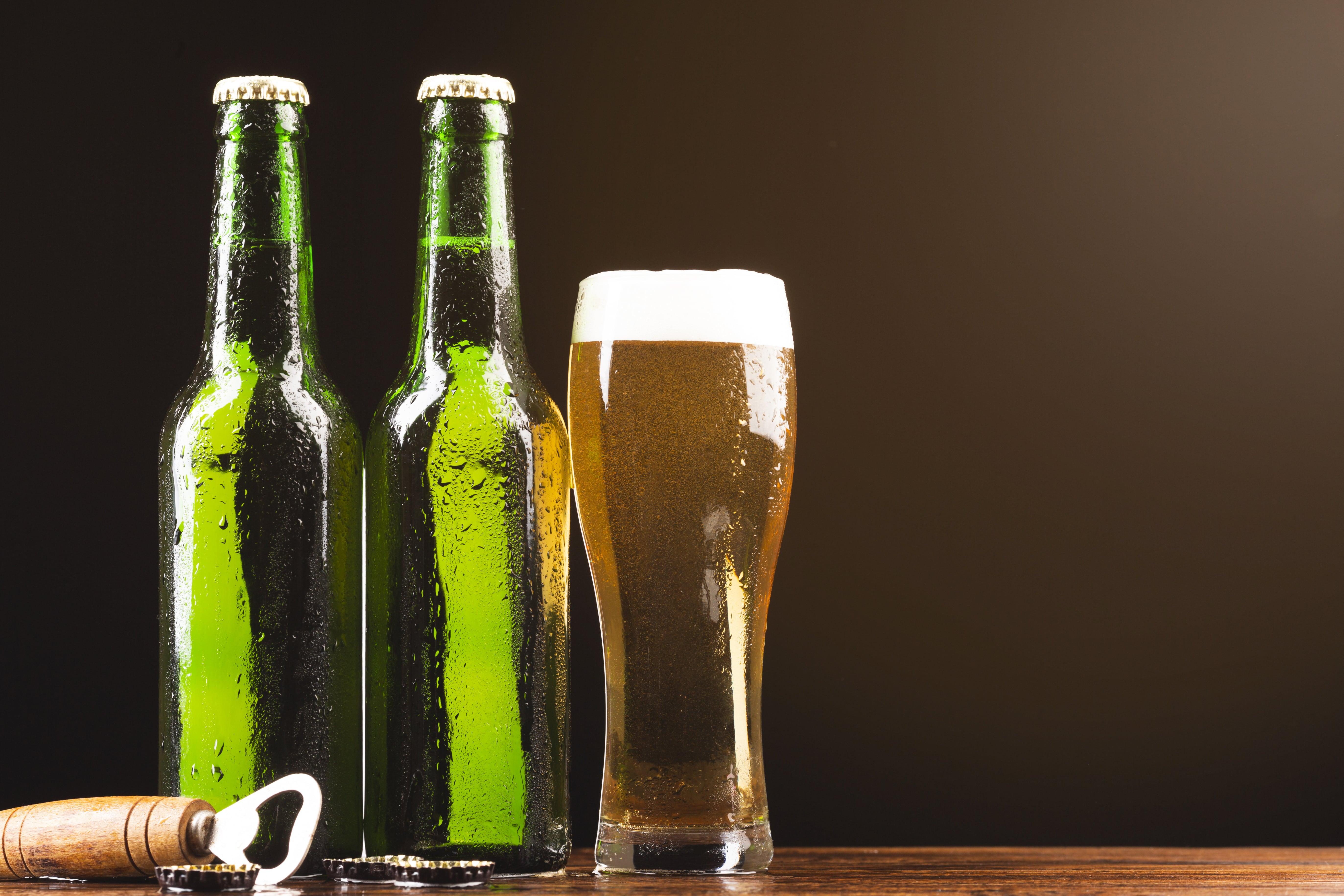 Duas garrafas de vidro de cerveja com um copo cheio de cerveja ao lado e um abridor de cerveja.