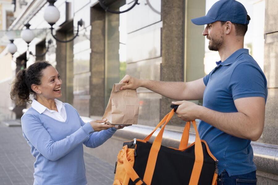 O motoboy entregando o pedido para o cliente, que está sorrindo.
