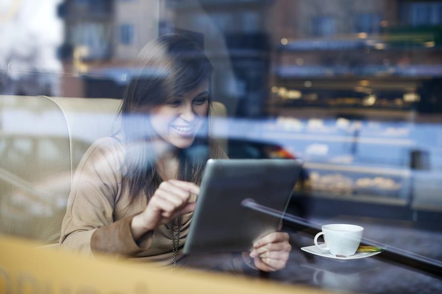 Mulher segurando um tablet com cardápio online em um café