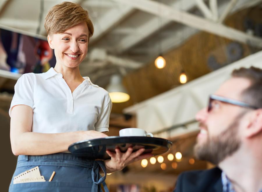 Garçonete sorridente atendendo um cliente em um restaurante.