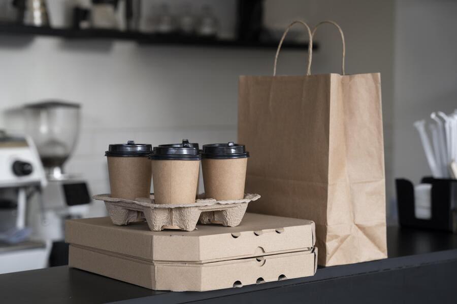Uma sacola, duas embalagens de pizza e 4 copos em cima de uma balcão na cozinha.