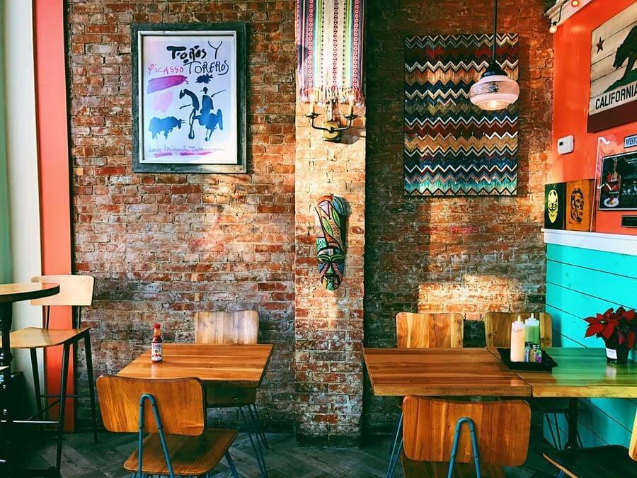 Restaurante temático com duas mesas e cadeiras e decoração na parede.